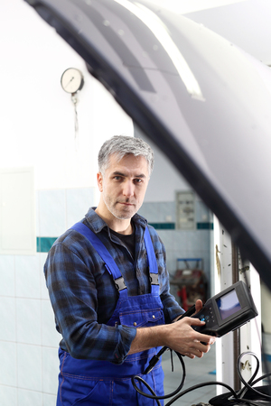 mechanics: Engine diagnostics. Car in diagnostic station, mechanic connected device Stock Photo