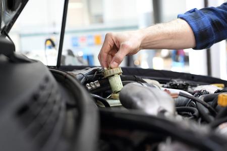 El mecánico de coches tensó la válvula bajo la capota de un automóvil. Foto de archivo