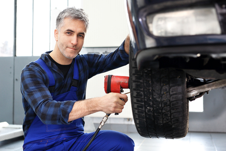 tightened: Tire service. Car mechanic tightened wrench pneumatic wheels in the car. Stock Photo