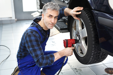 tightened: Mechanic adjusts the wheel alignment. Car mechanic tightened wrench pneumatic wheels in the car.