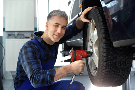 tightened: Car repair shop, tire service. Car mechanic tightened wrench pneumatic wheels in the car. Stock Photo