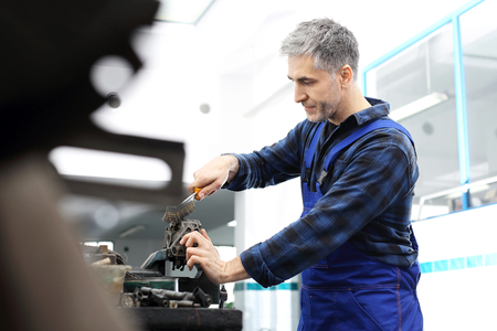 vise: man in the garage with a wire brush cleans mechanical parts Stock Photo