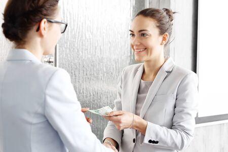remuneraciÓn: La remuneración por un trabajo bien hecho. Una mujer paga el empleado.