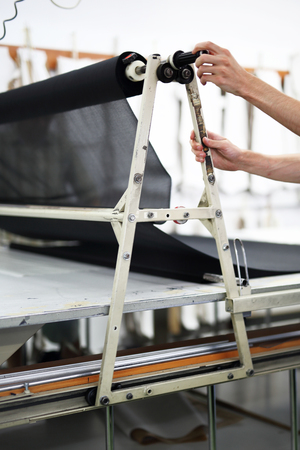 lagging: Lagging machine. Sewing worker lags material Stock Photo