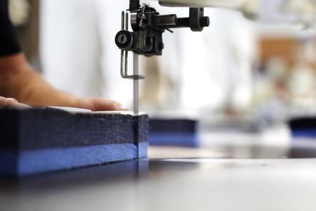 Cutting the fabric, sewing work.Cutting room, cutting cloth tailoring knife. Фото со стока
