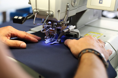 Sewing navy in a tailors shop.The production plant, sewing clothes by seamstresses on the sewing machine