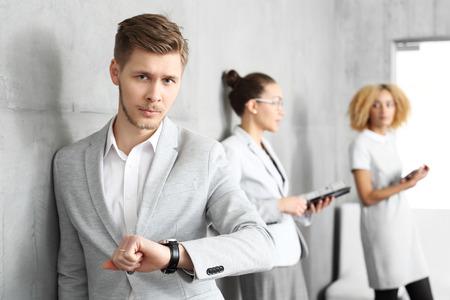 El tiempo es dinero. Joven revisar su reloj mientras estaba de pie en el pasillo fuera de la oficina. Foto de archivo