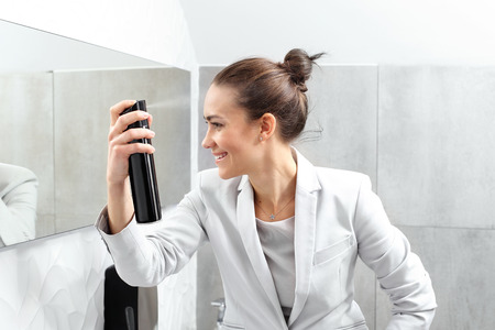 lacquered: Elegant office worker. Business woman combing her hair and lacquered in a company toilet. Stock Photo
