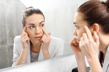 Reflectie in de spiegel. De vrouw kijkt in de spiegel en merk de eerste rimpels op Stockfoto