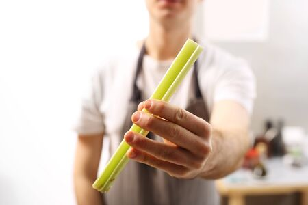 vegetable cook: Celery. The cook holds in his hand a vegetable.