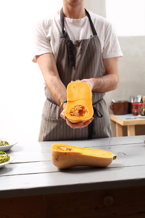 Pumpkin in the kitchen. The cook holds in his hand mature butternut squash. Stock Photo