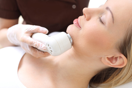 forcing: Ultrasound, a woman in the beauty salon. Light acne treatment, the woman in the beauty salon Stock Photo
