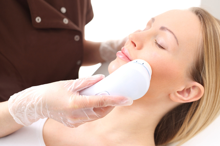 Peeling machine. Beauty salon pays heads to the womans face. Stock Photo