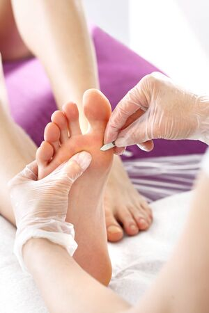 Podology. The Doctor Removes the imprint on the foot with a scalpel