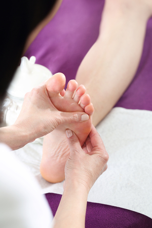rapprochement: Acupressure, foot massage. Woman in a beauty salon for a pedicure and foot massage.