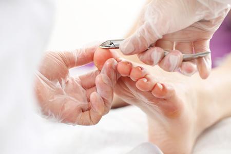 美容室でプロのペディキュア。美容師は指の爪で皮膚をカットし、プロのペディキュアを実行します。 写真素材 - 77382107