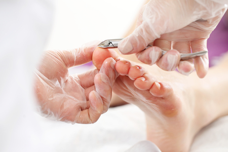 Professional pedicure in the beauty salon. The beautician cuts the skin with fingernails and performs professional pedicure.