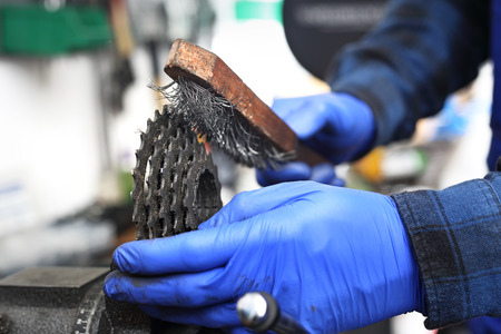 Cleaning the bicycle chain transmission.The bike mechanic in the service lubricates the bicycle with grease. Stock Photo