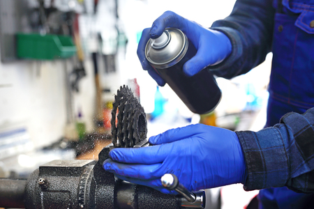 hubs: Bike service. Prepare your bike for the cycling season.The mechanic in the bike service lubricates the bicycle with grease. Stock Photo