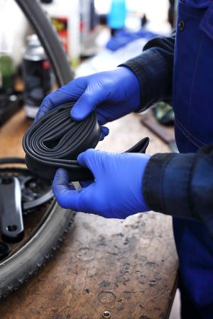 Bike service, mechanic replaces the inner tube Banco de Imagens