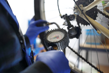 Pumping the bicycle wheel. The bike mechanic in the service of the pumped bike wheel with a compressed air compressor.