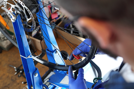 centering: Centering wheels on a bike. The service provider repairs the bike in the bike service.