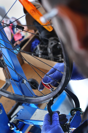 centering: Replacing a tire in a bicycle. The service provider repairs the bike in the bike service.