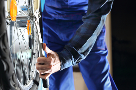 centering: Bike service, hub repair. The service provider repairs the bike in the bike service. Stock Photo