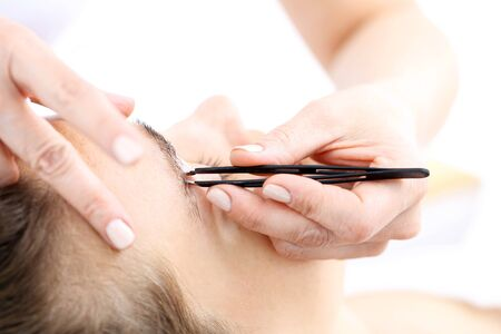 Eyebrow tweezers. Beauty depilated eyebrows clients, giving them the right shape
