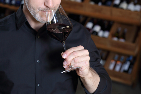 Red wine, man evaluates the color of wine in a glass.A handsome man judges the color of red wine.