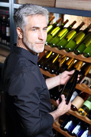 Wine cellar. Man chooses a bottle of white wine. Stock Photo