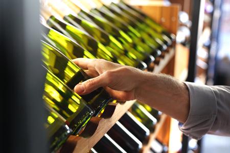 Wine. Man chooses a bottle of white wine.
