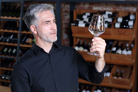 The bartender cleans the glass. A handsome bartender polishes a glass of wine glasses.