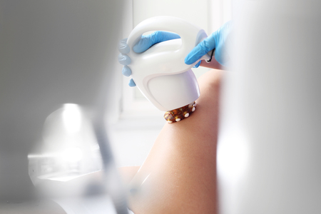 imperfection: Cosmetic salon, thigh skin care.Woman in the clinic of aesthetic medicine on the firming treatment and reducing the imperfection of the silhouette.