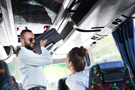 Suitcase. A handsome man helping a woman put her luggage on a shelf in a coach. Stock Photo - 80259771