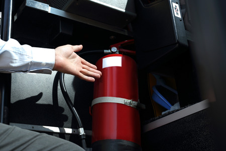 Car fire extinguisher. The bus driver checks the fire extinguisher. Stockfoto
