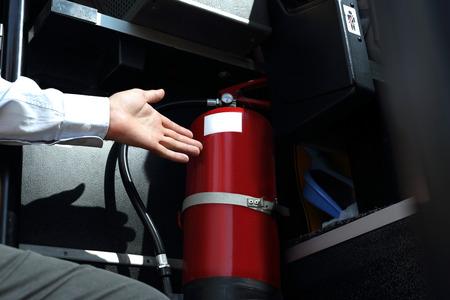 Car fire extinguisher. The bus driver checks the fire extinguisher. Archivio Fotografico