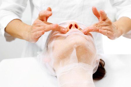 Skin care of the face in the beauty salon. A beautician puts a preparation on a womans face.