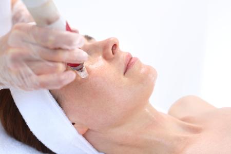 뷰티 살롱에서 바늘 mesotherapy 치료 미적 실행. 미용사는 여자의 얼굴에 바늘 mesotherapy 치료를 수행합니다.