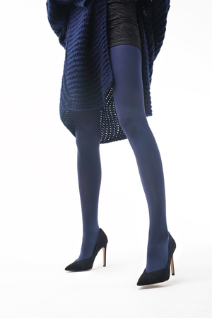 Colorful tights. Winter tights. Beautiful and shapely legs of a woman in opaque tights.