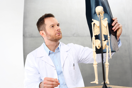 Orthopaedist. A doctor in the office is watching an x-ray of a patient. Stock Photo