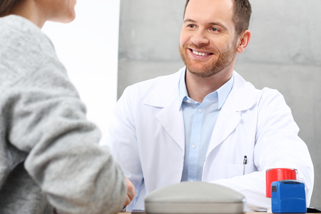 Smiling doctor talking with a patient. Imagens