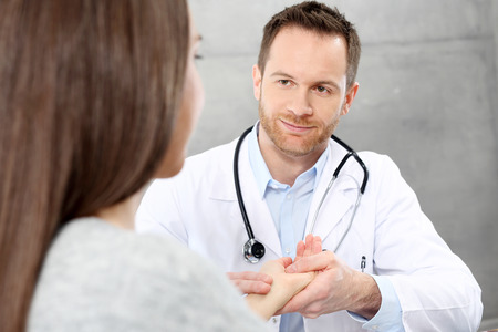 Visit the doctor. The doctor examines the patient's heart rate by holding his wrist.