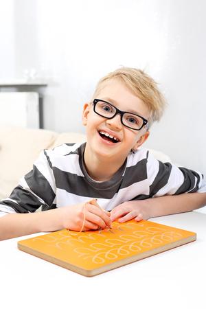 Education of a pre-school child. Smiling boy practicing writing letters. Foto de archivo