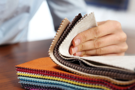 Upholstery fabrics. The woman watches the colors and patterns of upholstery fabrics.