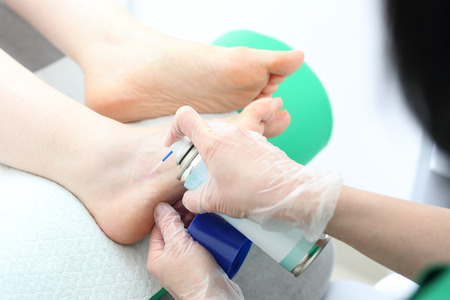 Ankle injury. The doctor freezes the place of contusion with a spray for injuries