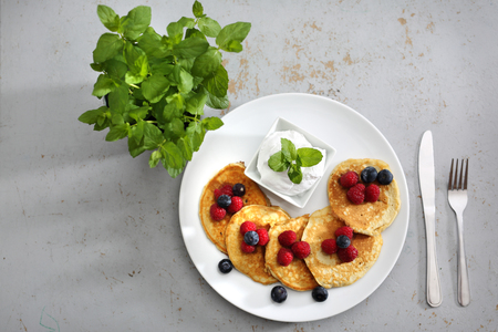 Fruit pancakes. A portion of tasty pancakes with berries, served with yoghurt sauce
