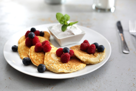 sweet breakfast. A portion of tasty pancakes with berries, served with yoghurt sauce
