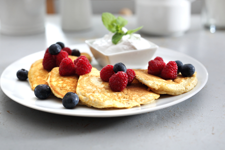 Pancakes with raspberries and blueberries. A portion of tasty pancakes with berries, served with yoghurt sauce