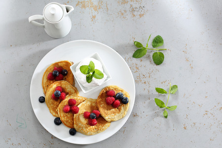 Pancakes, diet pancakes with fruit. A portion of tasty pancakes with berries, served with yoghurt sauce